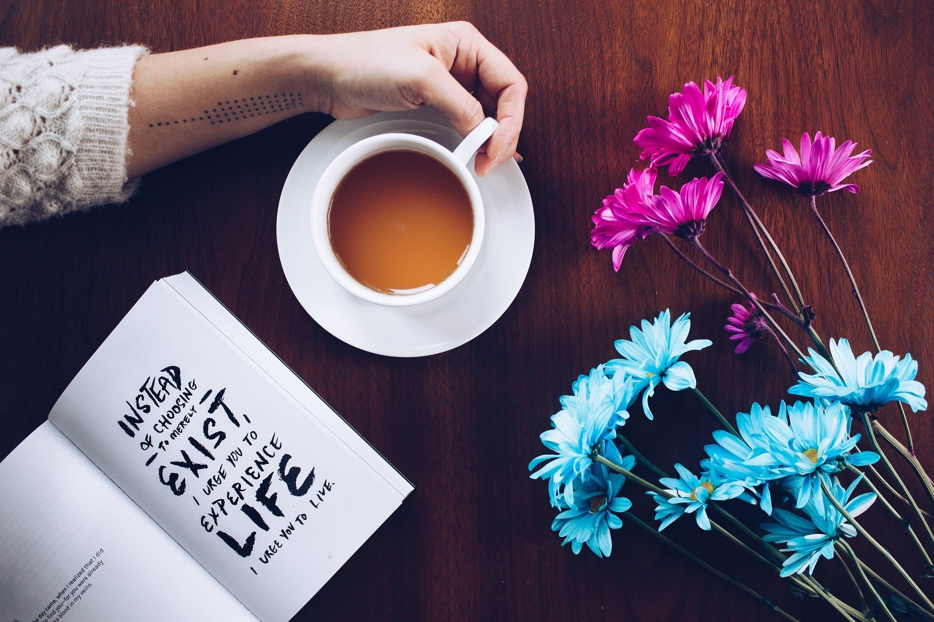 table with open book of quotes, flowers and tea