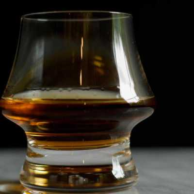 A glass of bourbon neat set on marble against a black background.
