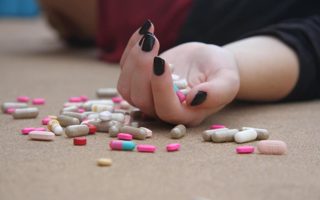 Woman lying on floor with a handful of pills