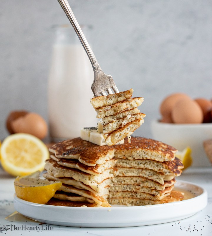 Stack of lemon pancakes, cut, with fork.