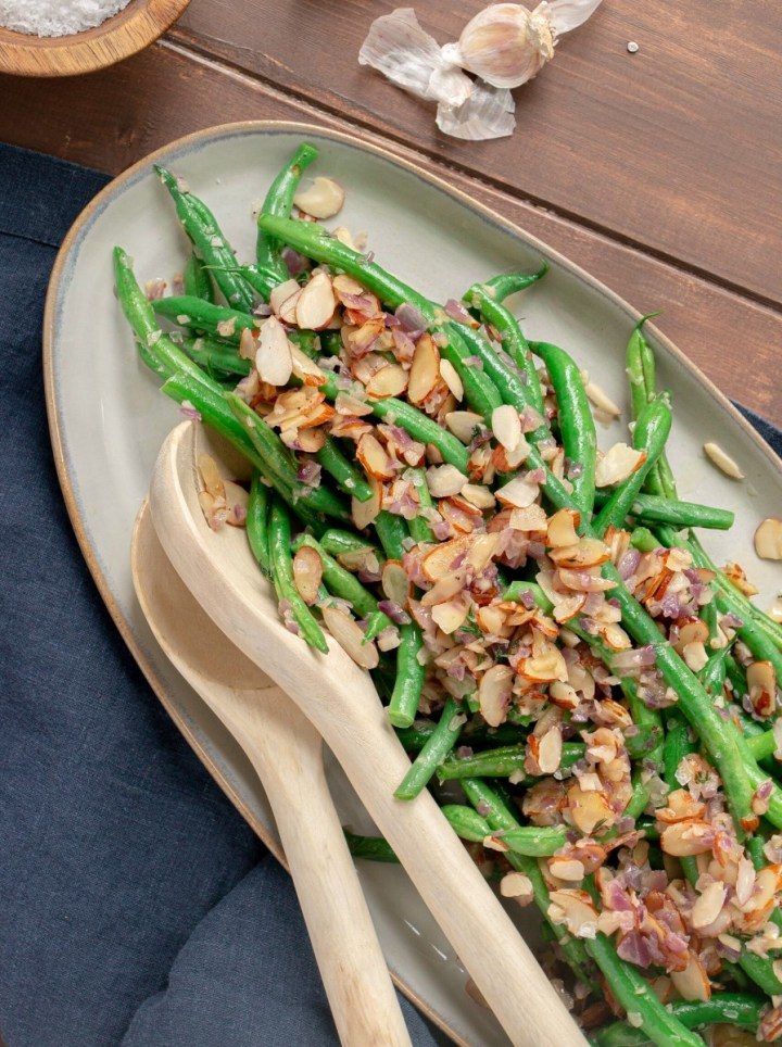 fresh green beans on a platter with sautéed almonds, red onion, and garlic.