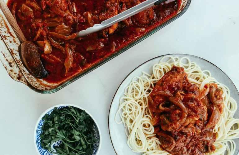 spaghetti with tomato sauce in white ceramic plate