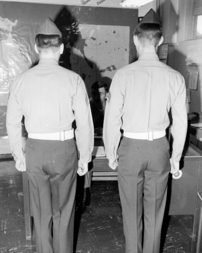 Adak [rear view of two servicemen standing at attention in front of desk where third man is seated; map on wall]