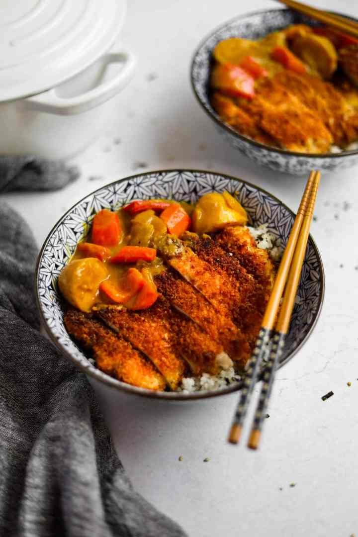Chicken Katsu Curry in a blue Japanese porcelain bowl with blue and wood bamboo chopsticks and a white Le Creuset dutch oven