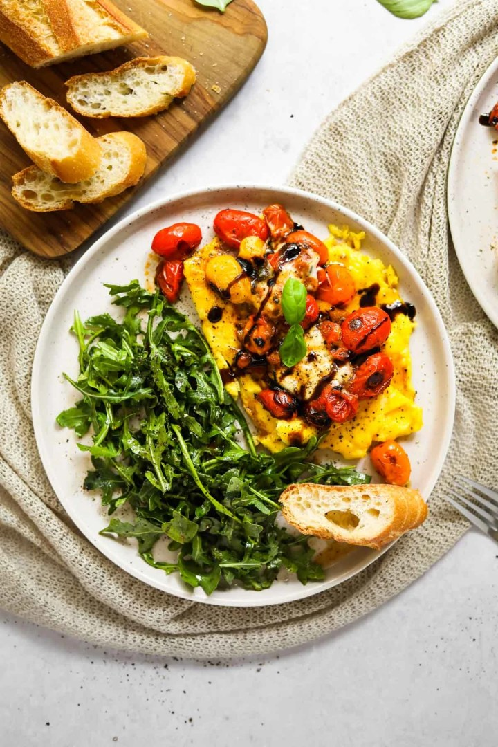 Soft-scrambled eggs with burrata, blistered tomatoes, arugula and a toasted baguette