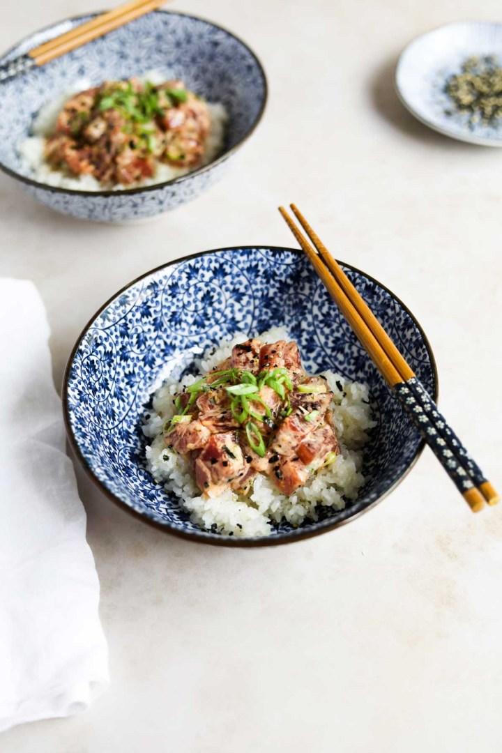 Spicy ahi tuna poke bowl with chopsticks in a blue Japanese bowl.