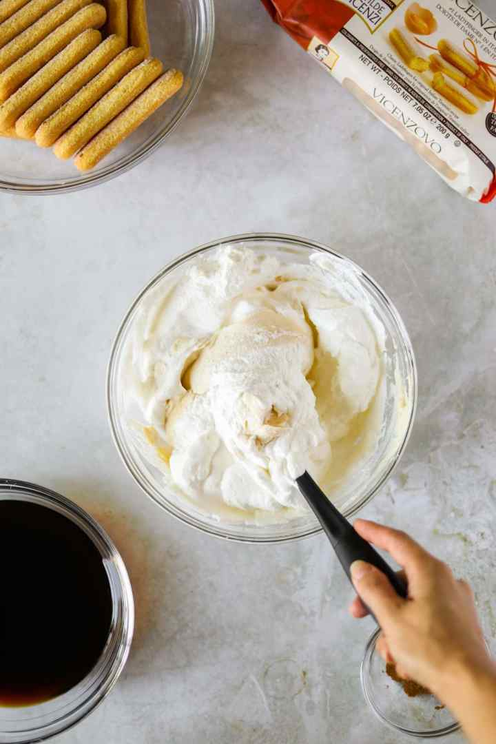 Mascarpone cheese and whipped cream being folded into a glass mixing bowl with a silicone spatula