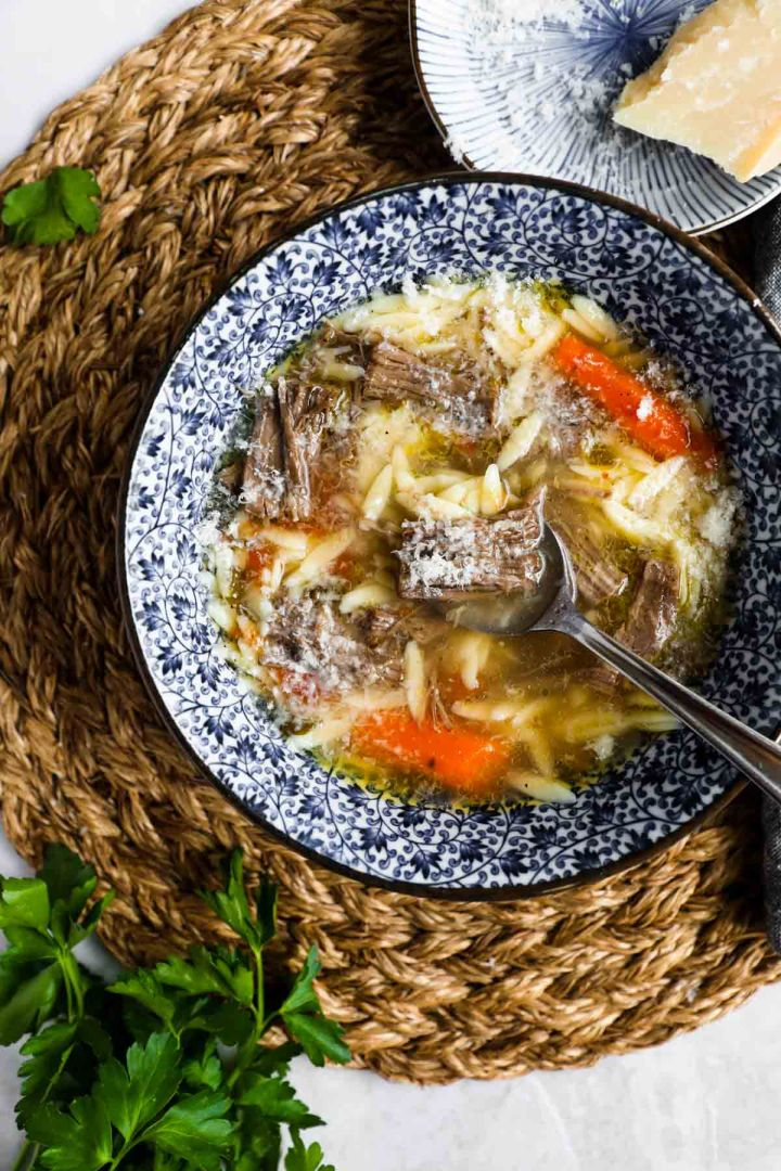 Italian beef soup (brodo di carne) in blue and white bowl.