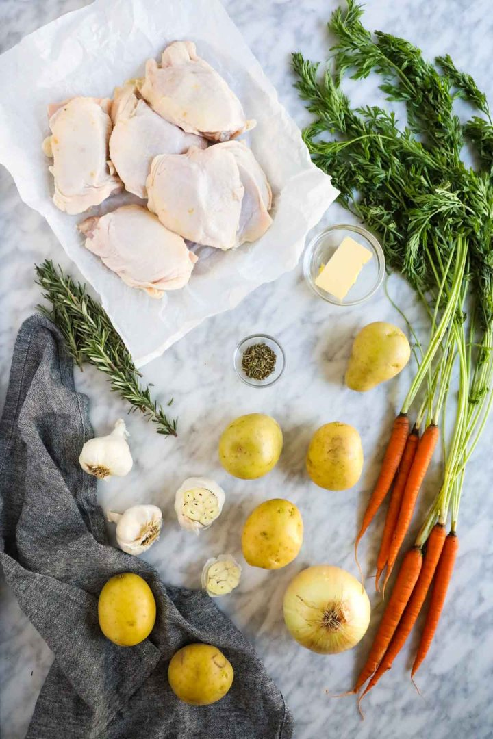 Raw Chicken Thighs with potatoes, garlic, butter, carrots, rosemary, and onion.