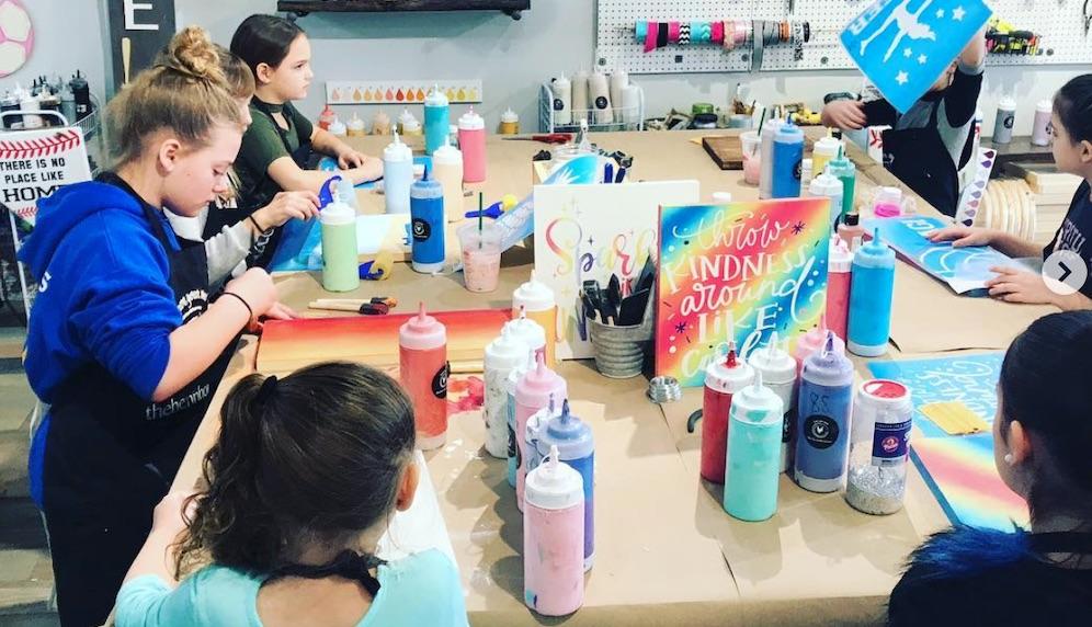 Kids making custom wood signs at a DIY workshop