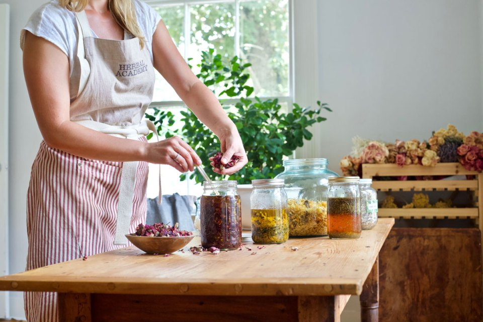 a woman making herb-infused oils