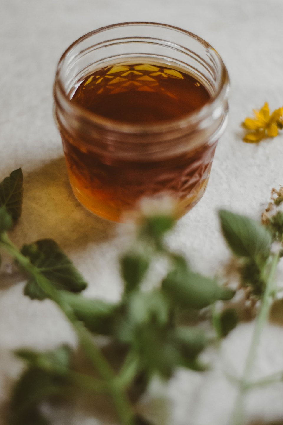 Golden oil surrounded by St. John's wort flowers and leaves