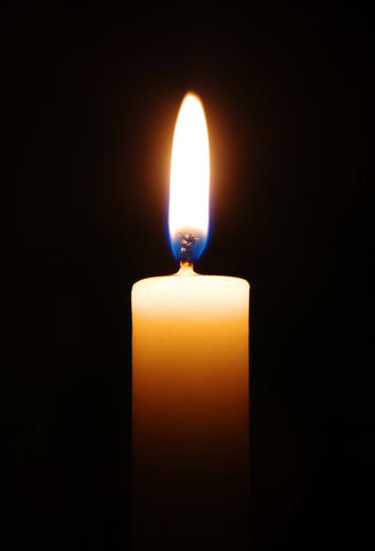 Single burning candle surrounded by blackness