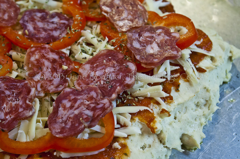 After rising, the dough now has a coating of sauce, cheese, bell peppers and salami