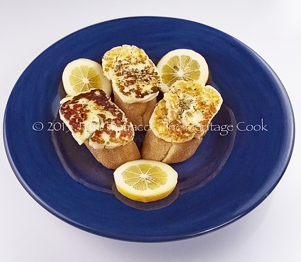 Grilled Halloumi cheese on baguette slices, drizzled with fresh lemon juice