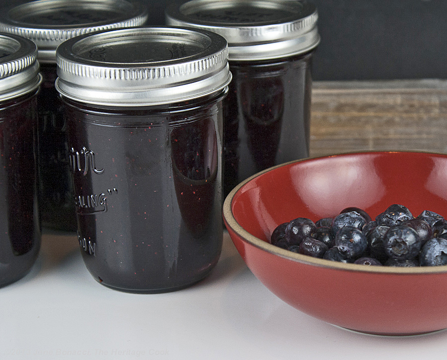Homemade Blueberry Jam from The Heritage Cook; jars next to bowl of berries