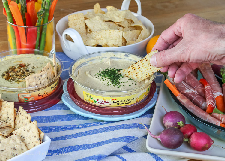 Hand dipping chip in hummus; Sabra's Unofficial Meal for Casual Gatherings; © 2016 Jane Bonacci, The Heritage Cook