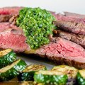 Close up of chimichurri sauce on slices of flank steak & sauteed zucchini; Flank Steak with Fresh Chimichurri Sauce #ProgressiveEats © 2017 Jane Bonacci, The Heritage Cook