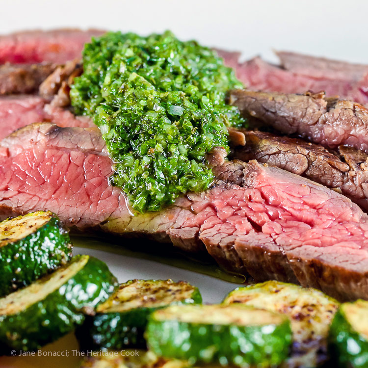 Close up of chimichurri sauce on slices of flank steak & sauteed zucchini; Flank Steak with Fresh Chimichurri Sauce #ProgressiveEats © 2017 Jane Bonacci, The Heritage Cook