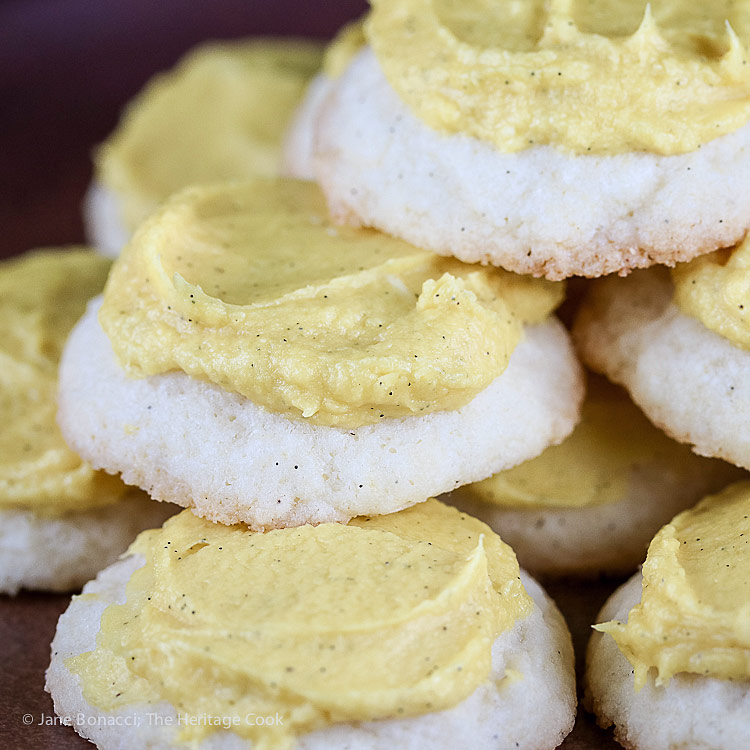 Close up of a cookie pile; Lemon White Chocolate Sugar Cookies with Lemon Buttercream Frosting © 2018 Jane Bonacci, The Heritage Cook