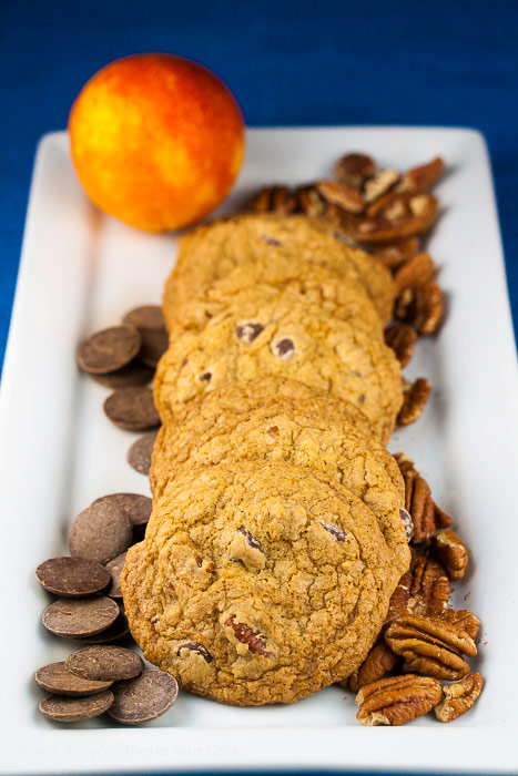 Platter of cookies surrounded by chocolate chips and pecans; Orange Scented Gluten Free Chocolate Chip Cookies © 2018 Jane Bonacci, The Heritage Cook