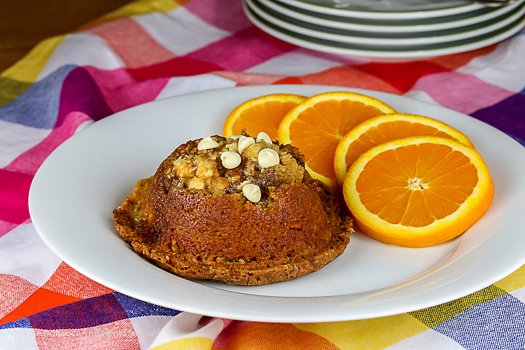 coffee cake muffin on plate with sliced oranges and stack of plates in back; Coffee Cake Muffins © 2019 Jane Bonacci, The Heritage Cook