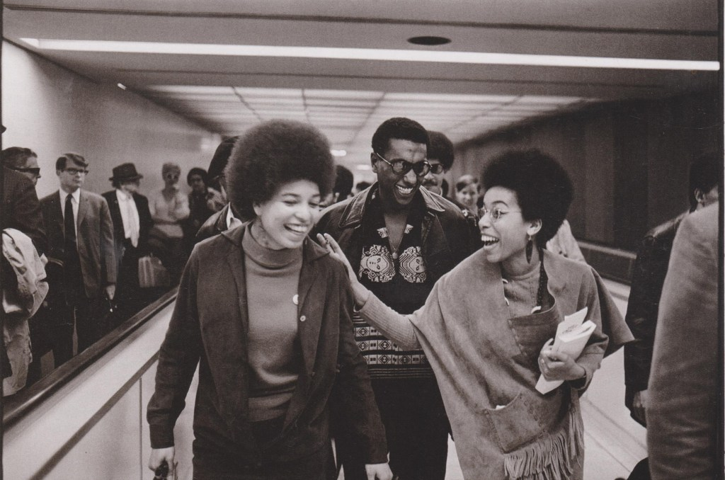 Activist Angela Davis (left), Black Panther Barbara Easley Cox, and Stokely Carmichael at the Los Angeles International Airport. (Photo Credit: Howard Bingham, 1968)