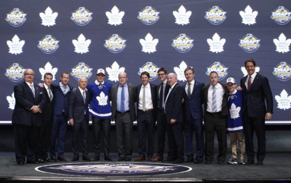 Auston Matthews linked arm and arm with the Toronto Maple Leafs' management team pose for a picture after drafting Auston Matthews first overall in the 2016 NHL Entry Draft.