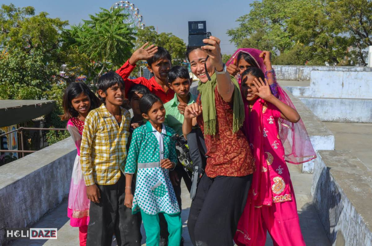 Christine Kaaloa of Grrrl Traveler taking a selfie with a group of young kids in Pushkar, India