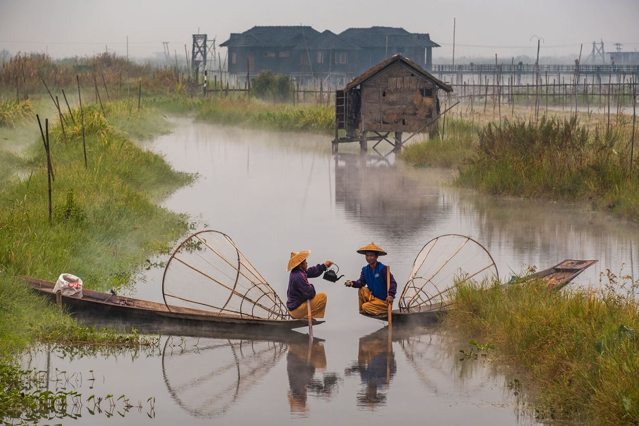 Local fisherman drink tea in their boats on a cold misty morning at Inle Lake, Myanmar