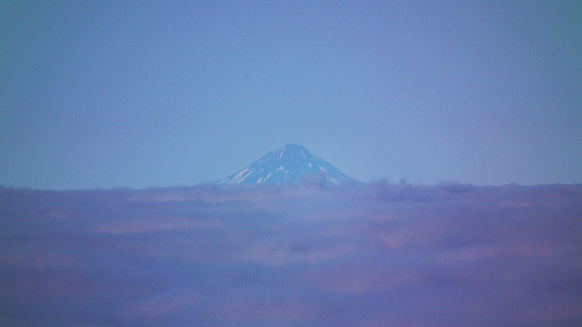 Mount Taranaki's summit on the horizon, a hundred miles away