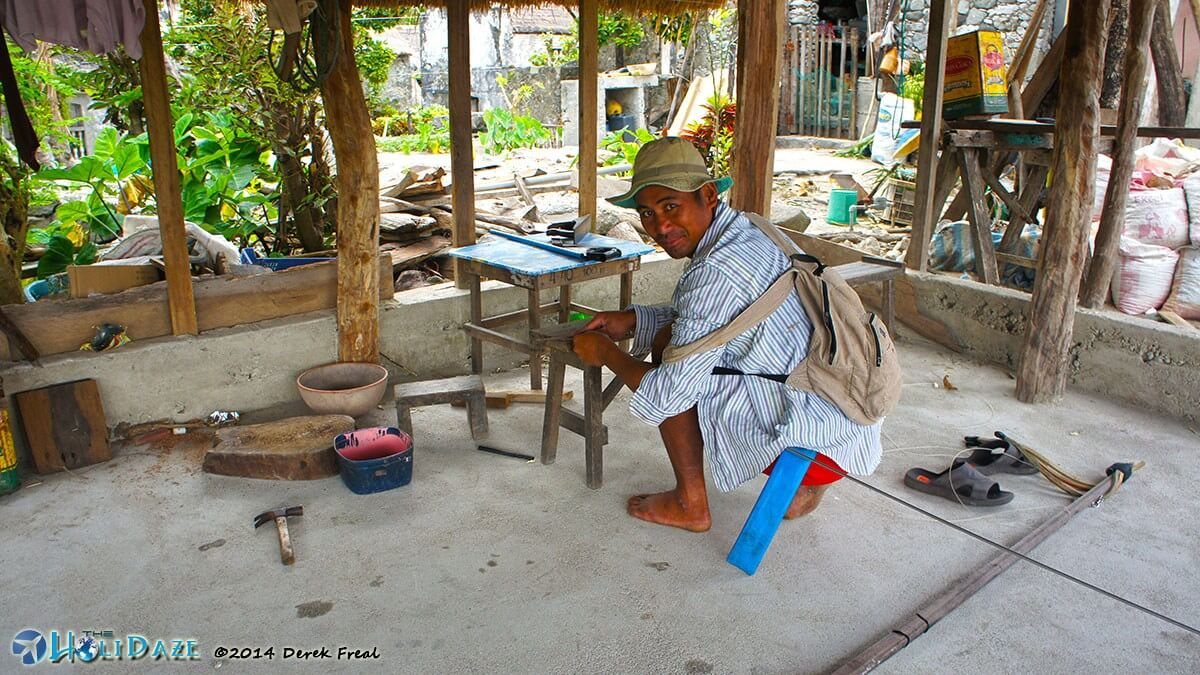 Local man sharpening a metal rod for use with his traditional Ivatan spear gun in Chavayan village, Philippines