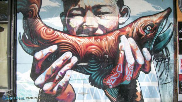 Street art of a man eating a fish at Graffiti Alley, Toronto, Canada