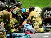 Volunteer_firefighters_treat_a_car_wreck_victim