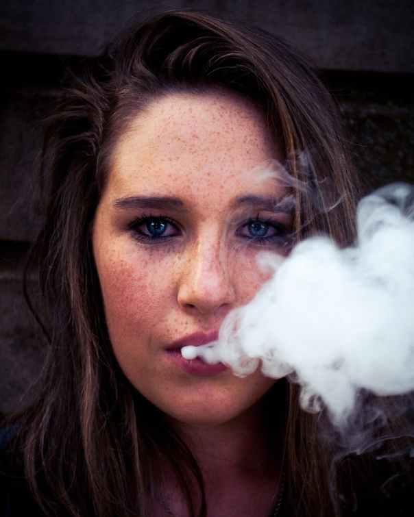 woman taking selfie while smoking