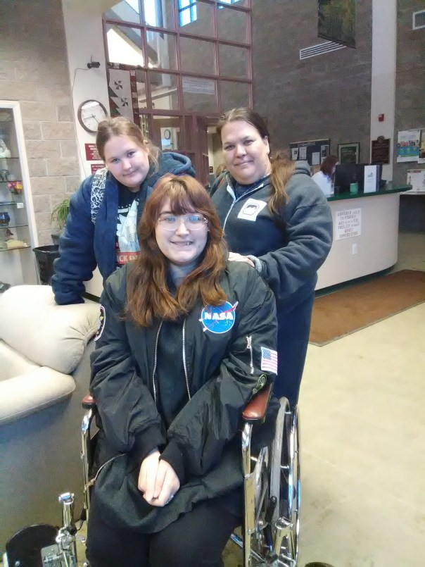 young woman smiling in wheelchair with mom and sister standing behind her.