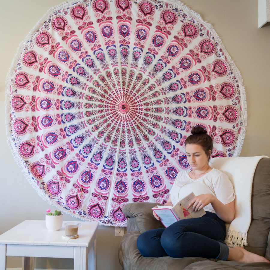 woman sits in front of pink hanging tapestry while reading a book.