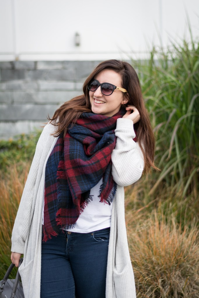 woman wears plaid blanket scarf and eco friendly sunglasses