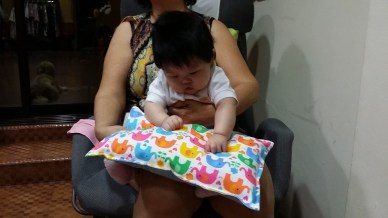 Baby V sitting on Mamak's lap and fascinated with the striking colours and soft fabric of the cottony pillow!