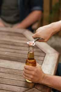 man taking off cap of beer bottle with opener