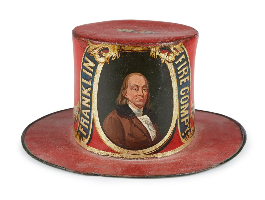 A painted and decorated leather and felt parade hat for the Franklin Fire Company, a volunteer fire-fighting company which was active in Germantown, Philadelphia, Pennsylvania. It dates to between 1840 and 1860, stands six and a half inches tall, and measures a bit over 13 inches in diameter.
