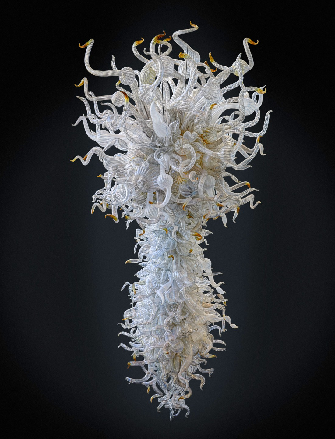 A white, clear, and amber chandelier, measuring ten feet tall, five feet wide, and four feet, eight inches deep, made by Dale Chihuly in 2004.