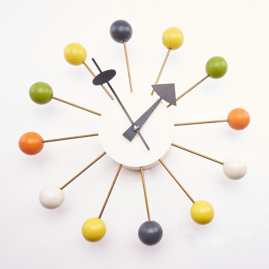 "George Nelson's ball wall clock is a mid-century design icon. It resembles a sun with rays streaming from it. Each of the twelve ""rays"" ends with a ball that represents an hour. This particular version featured balls that had different colors: black, green, yellow, white, and orange."