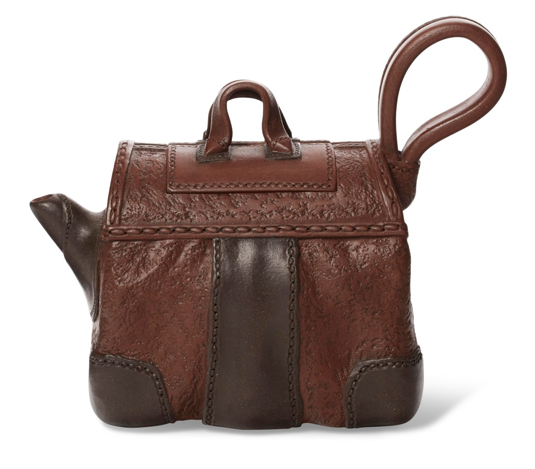 """A small baggage-form teapot with cover by contemporary Yixing [pronounced Yee-shing] potter Zhou Dingfang [pronounced Jo Ding-fong]. It looks for all the world like a little suitcase made from milk chocolate-colored leather with dark chocolate-leather patches and accents. The only hint that it's a teapot are the looped handle, which resembles leather, and the spout on the left side of the """"bag""""."""