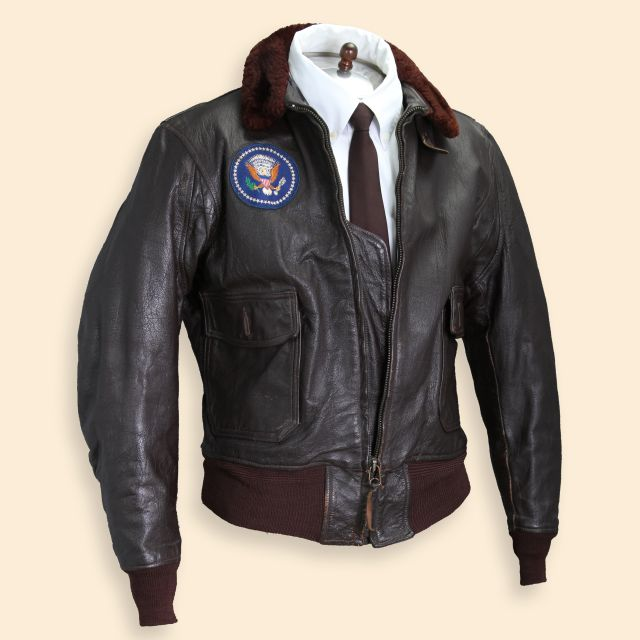 An Air Force One brown leather bomber jacket worn by President John F. Kennedy, shown in full.