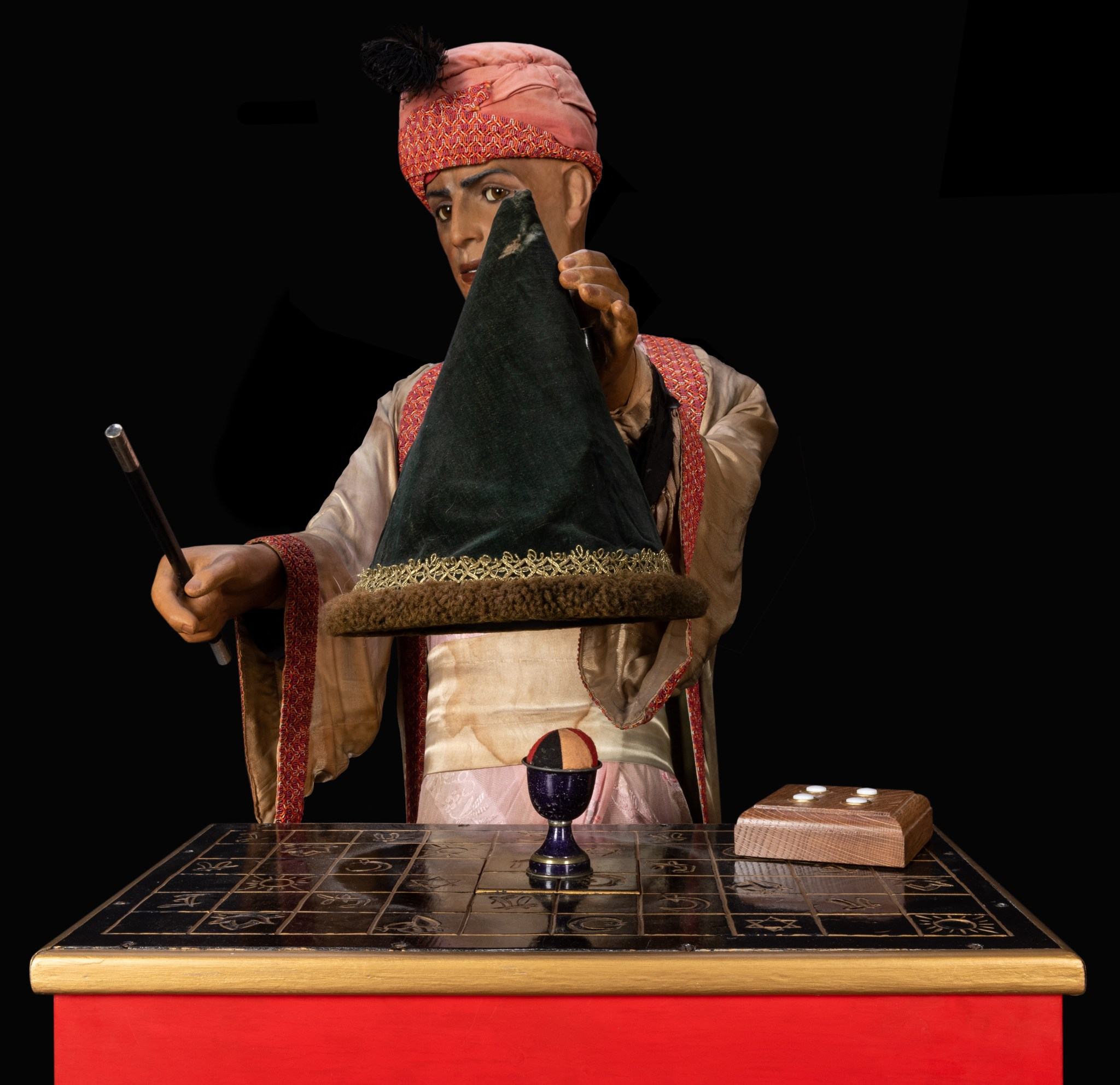 The magician automaton from Sleuth, shown lifting a wizard's cap.