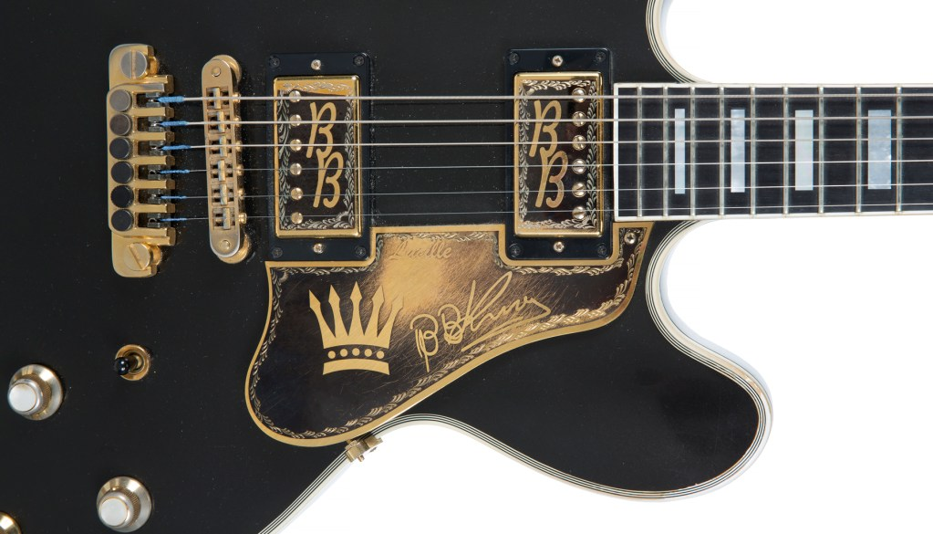 A closeup on the body of the B.B. King Lucille guitar, showing the decorative crown and the bluesman's signature, rendered in gold on gold.