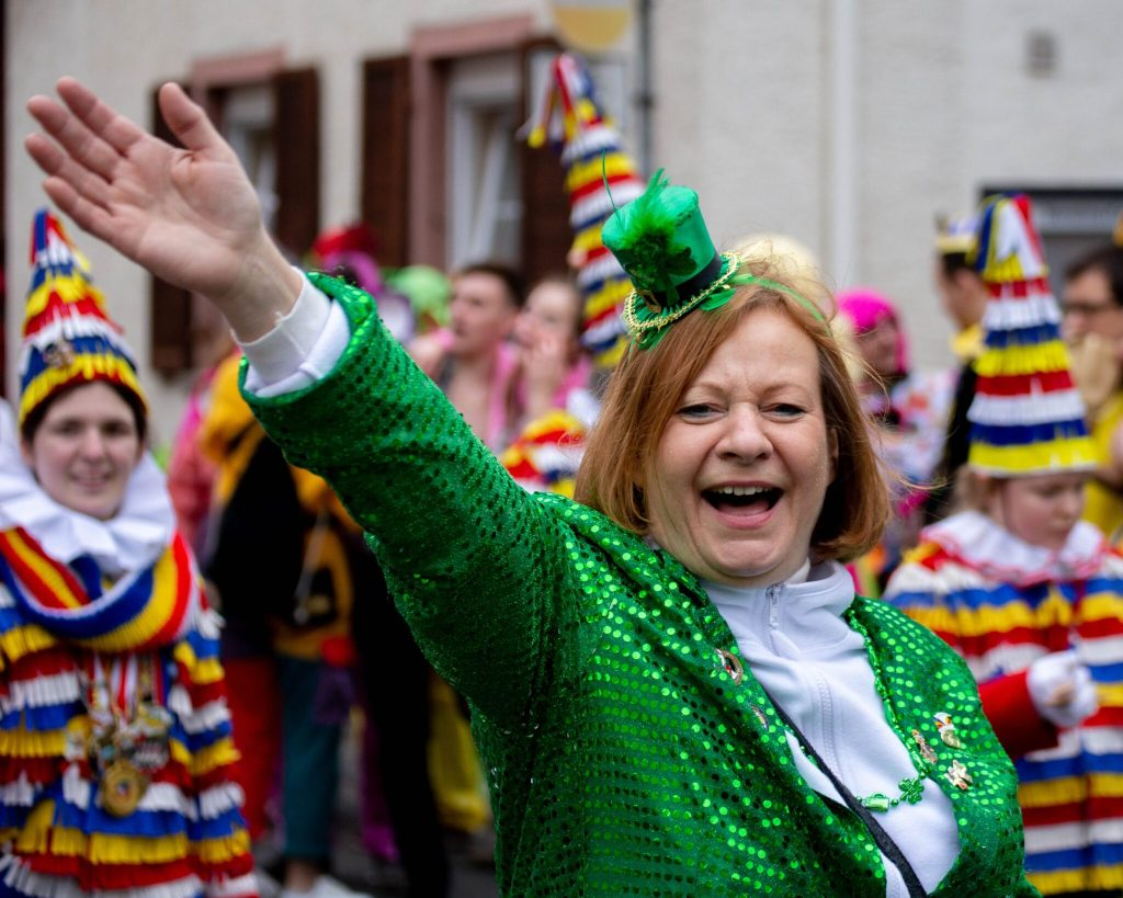 Irish, woman waving wearing green hat and jacket