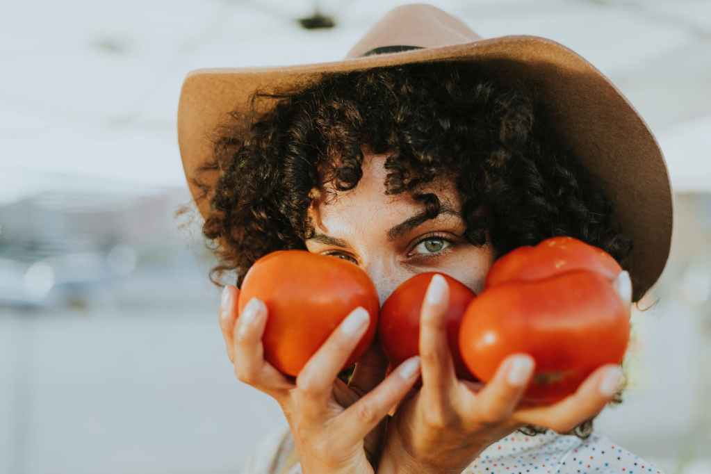 Gardening ideas, lady in hat with tomatoes