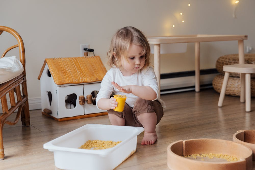 Sensory play station, child playing with bin